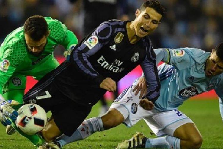 Pemain Real Madrid, Cristiano Ronaldo, terlibat dalam perebutan bola dengan kiper dan bek Celta Vigo, Sergio Alvarez dan Facundo Roncaglia, pada laga Copa del Rey di Balaidos, Rabu (25/1/2017).