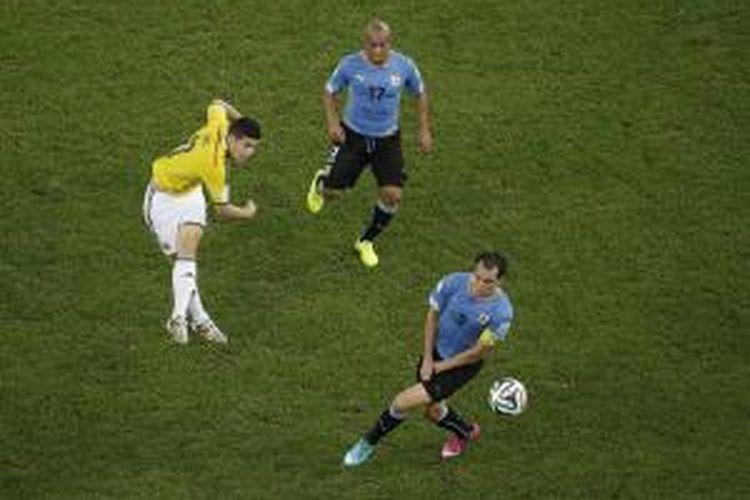 Penyerang Kolombia, James Rodriguez (kiri), melepaskan tembakan yang berujung gol pertama (dari dua) ke gawang Uruguay, pada pertandingan 16 besar Piala Dunia, di Estadio Do Maracana, Rio De Janeiro, Sabtu (28/6/2014).