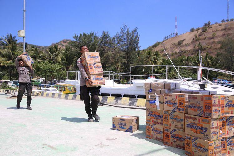 Dua anggota polisi terlihat menggotong bantuan makanan instan bagi warga yang bertahan di Pulau Gili Trawangan, Nusa Tenggara Barat (NTB), setelah rentetan gempa mengguncang kawasan ini dengan gempa utama pada Minggu (5/8/2018). Bantuan ini dikirimkan pada Kamis (9/8/2018).