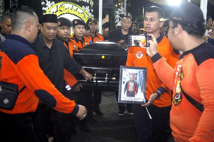 Jenazah Kepala Pusat Data Informasi dan Humas Badan Nasional Penanggulangan Bencana (BNPB) Sutopo Purwo Nugroho diusung oleh personel BNPB untuk diberangkatkan ke Boyolali dari Raffles Hils, Cimanggis, di Depok, Jawa Barat, Senin (8/7/2019) dini hari. Jenazah dibawa kembali setelah disemayamkan di rumah duka untuk dimakamkan di Boyolali, Jawa Tengah.