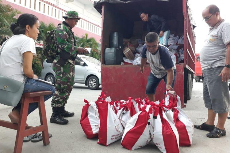 Petugas menurunkan paket bantuan untuk pengungsi dari kendaraan pengangkut yang dikawal prajurit TNI, Selasa (2/10/2018).