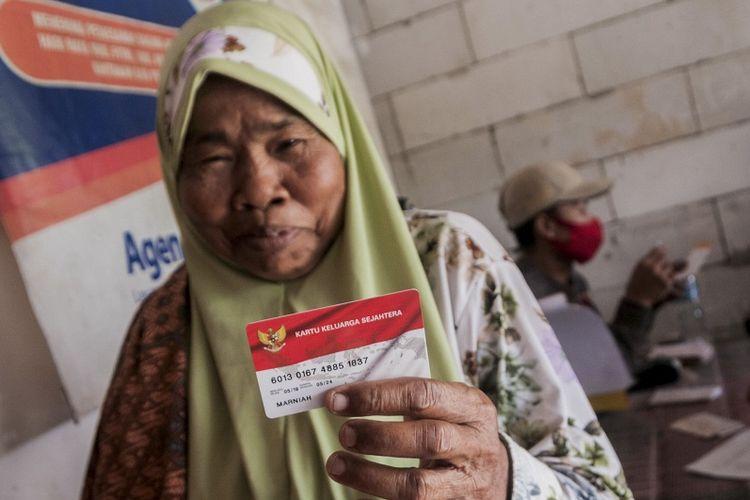 Warga menunjukkan Kartu Keluarga Sejahtera saat penyaluran bantuan sosial Program Keluarga Harapan (PKH) di Desa Margajaya, Lebak, Banten, Selasa (6/10/2020). Kementerian Sosial memastikan bantuan bagi penerima kartu sembako dan Program Keluarga Harapan (PKH) akan berlanjut hingga 2021 jika pandemi COVID-19 belum berakhir sebagai upaya memberikan perlindungan sosial bagi masyarakat terdampak pandemi COVID-19. ANTARA FOTO/Muhammad Bagus Khoirunas/agr/foc.