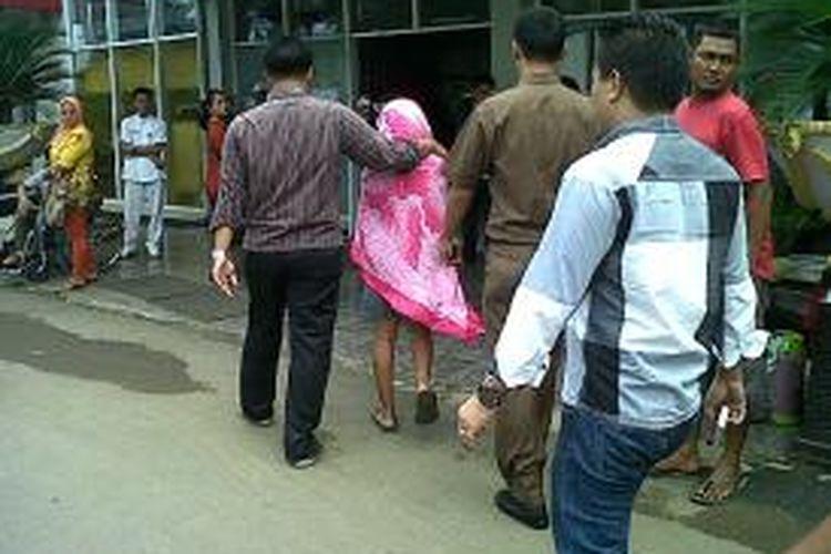 ER (15) tengah dievakuasi polisi ke Rumah Sakit Umun Daerah (RSUD) Tenriawaru, Kabupaten Bone, Sulawesi Selatan setelah diperkosa delapan pemuda. Kamis, (02/01/2014).