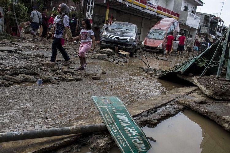 Sejumlah warga melintas di area pemukiman yang sempat terendam banjir di kawasan Pondok Gede Permai, Jati Asih, Bekasi, Jawa Barat, Kamis(2/1/2020). Banjir di kawasan tersebut, merupakan banjir terparah di wilayah Bekasi.