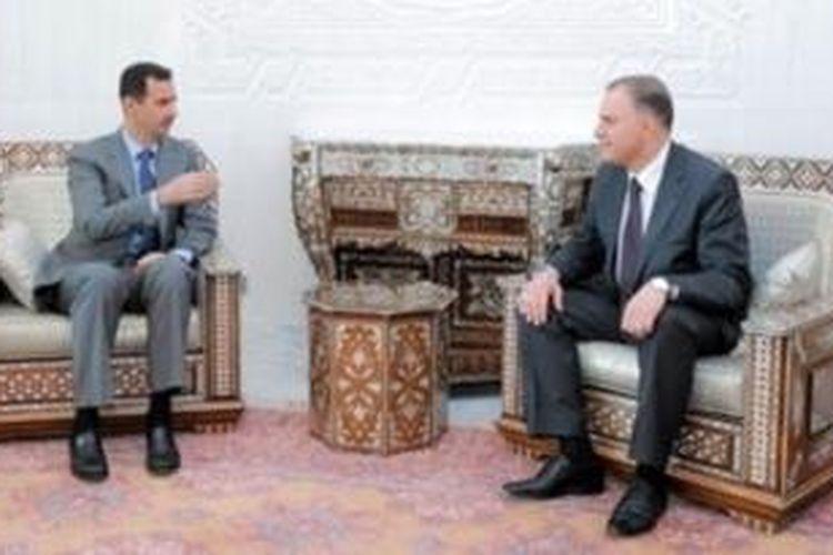 Foto ini menampilkan Presiden Suriah Bashar al-Assad saat menerima Gubernur Hama Anas Abdel Razzaq al-Naem pada Juli 2011. Gubernur Hama tewas dalam serangan bom mobil, Minggu (25/8/2013).