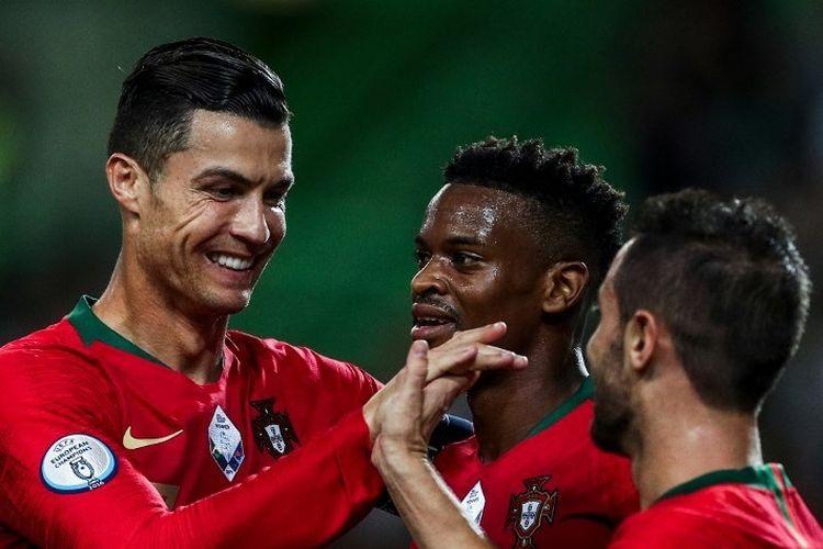 Cristiano Ronaldo dan Nelson Semedo merayakan gol Bernardo Silva pada pertandingan Portugal vs Luksemburg dalam lanjutan kualifikasi Euro 2020 di Lisbon, 11 Oktober 2019.