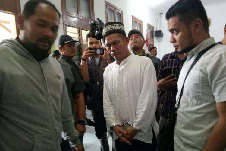 Asep Maftuh (45) yang tampak mengenakan pakaian muslim tengah mendapatkan pengawalan usai menjalani sidang perdananya di Pengadilan Negeri (PN) Bandung, Jalan LLRE Martadinata, Kota Bandung, Kamis(24/5/2018). Asep didakwa Pembunuhan Berencana.