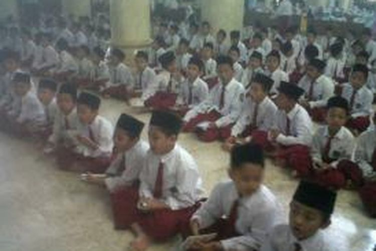 Ratusan Siswa- Siswi Madrasah Ibtidaiyah (MI) At Taqwa Bondowoso, Jawa Timur, mendoakan rekan mereka Tara (13), yang menjadi korban ledakan maut di Gang Malabar Kelurahan Kota Kulon, Bondowoso, Senin (30/9/13)