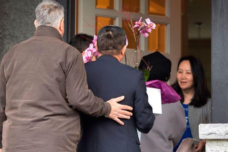 Chief Financial Officer Huawei Technologies Meng Wanzhou (kanan) menyambut kedatangan tamu usai dibebaskan dengan jaminan di rumahnya di Vancouver, British Columbia, Kanada, pada Selasa (12/12/2018). (AFP/Jason Redmond)