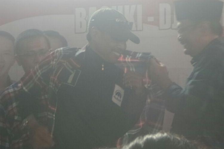 Calon wakil gubernur DKI Jakarta Djarot Saiful Hidayat memakaikan baju kotak-kotak kepada relawan Agus-Sylvi.
