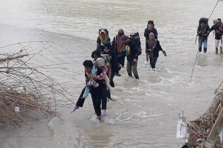 Relawan Muhammadiyah Disaster Managemen Centre (MDMC) menyeberangi sungai untuk mengantar logistik di pengungsian warga Desa Maipi, Kecamatan Masamba, luwu Utara, Senin (27/07/2020)