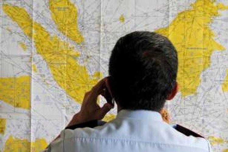 Petugas bandara memeriksa peta di Krisis Center hilangnya pesawat AirAsia QZ8501 di Bandara Juanda Surabaya, 28 Desember 2014. Pesawat AirAsia QZ8501 yang mengangkut 155 penumpang serta 7 awak, hilang kontak pada Minggu pagi, saat penerbangan dari Surabaya menuju Singapura.