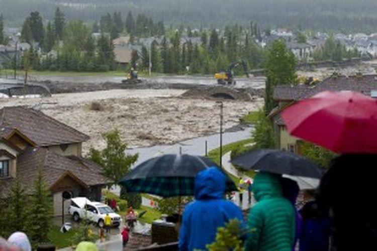 Warga menyaksikan banjir di Cougar Creek, Canmore, Alberta, Kanada, pada 20 Juni 2013. Banjir besar yang disebabkan hujan lebat itu telah menghanyutkan jembatan dan mendorong evakuasi ribuan orang.