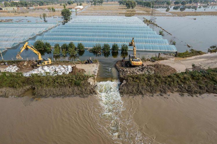 Kru penyelamat tengah melakukan penggalian jalan air dengan menggunakan ekskavator untuk merilis air banjir usai hujan deras di Jiexiu, Provinsi Shanxi, China utara.