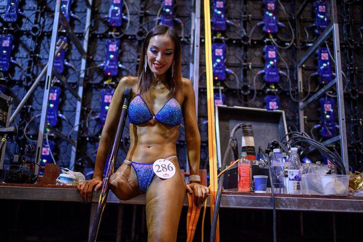 Foto tertanggal 11 Desember 2020 menunjukkan Gui Yuna, wanita binaraga berkaki satu asal China, sedang beristirahat di belakang arena kompetisi International Weightlifting Federation (IWF) Beijing 2020. Gui yang merupakan mantan atlet lompat jauh di Paralimpiade Athena 2004, baru menjalani debut di kompetisi binaraga dan langsung menang pada Oktober 2020.