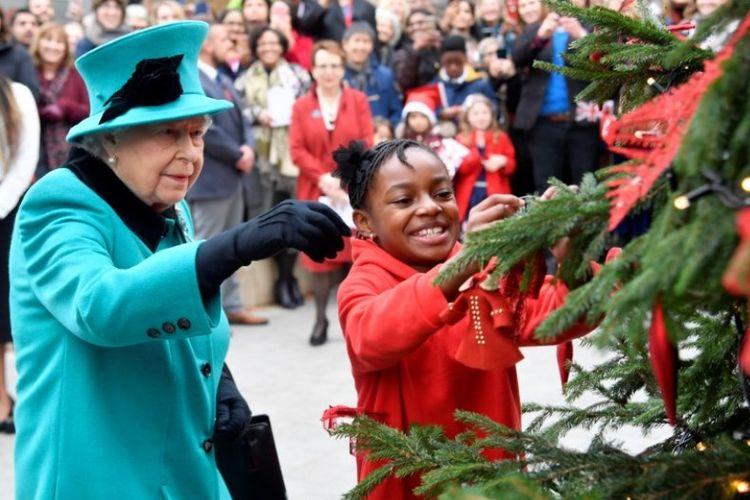 Ratu Elizabeth II dan Shylah Gordon menghias pohon natal. Ratu mengunjungi lembaga badan amal anak-anak Coram di London pada 5 Desember 2018. (AFP/TOBY MELVILLE)
