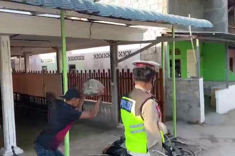 Dalam video itu, seorang Pria tampak melempar sepeda motor miliknya dengan menggunakan batu berukuran besar secara berulang.