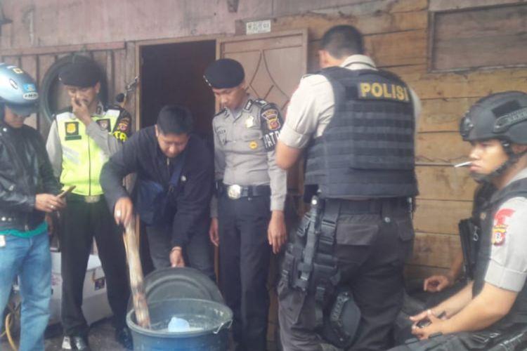Jajaran Polsek Jatinangor mengamankan jeriken tuak dari salah satu warung di Jalan Raya Bandung-Garut, Jumat (22/2/2019). Dok. Polres Sumedang