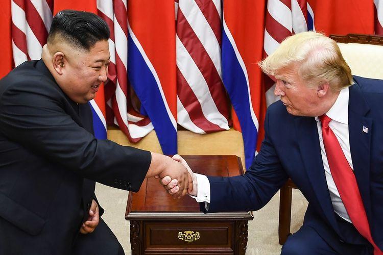 Pemimpin Korea Utara Kim Jong Un (kiri) berjabat tangan dengan Presiden AS Donald Trump usai pertemuan singkat di garis demarkasi militer, zona demiliterisasi di desa Panmunjom, Korea Selatan, Minggu (30/6/2019).