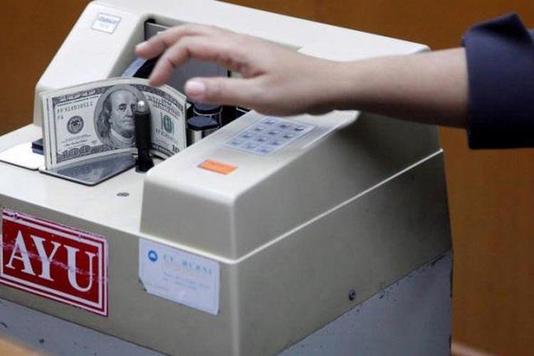 Petugas menghitung Dollar AS di tempat penukaran valuta asing PT. Ayu Masagung di Jakarta.