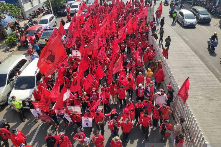 Massa PDIP Jakarta Timur melakukan aksi jalan kaki di Jalan Matraman Raya menuju Mapolrestro Jakarta Timur untuk menuntut pelaku pembakaran bendera partai ditangkap dan diadili sesuai hukum, Kamis (25/6/2020).