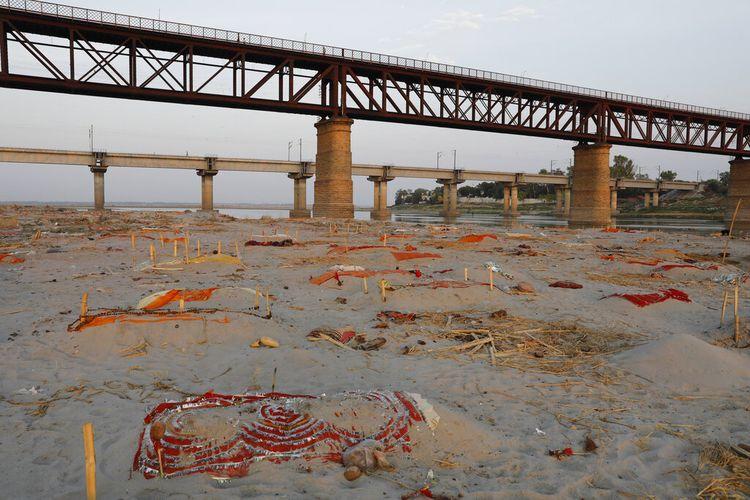 Mayat korban Covid-19 terlihat di kuburan dangkal yang terkubur di pasir dekat tempat kremasi di tepi Sungai Gangga di Prayagraj, India, Sabtu, 15 Mei 2021.