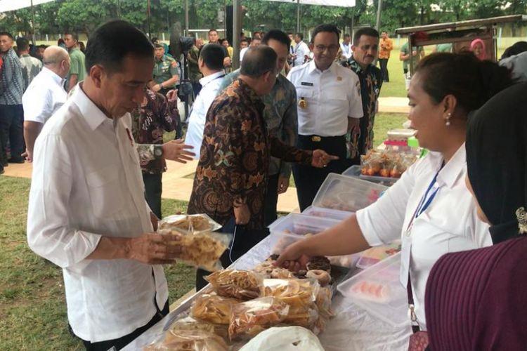Presiden Joko Widodo saat memborong dagangan ibu-ibu penerima PMN Mekaar, Ciracas, Jakarta Timur, Kamis (10/1/2019).