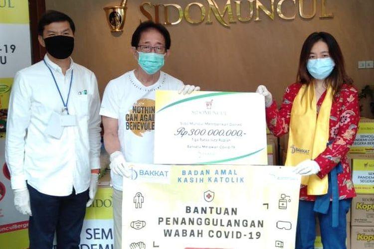 Direktur Sido Muncul Irwan Hidayat (tengah) memberikan bantuan penanggulangan wabah Covid-19 kepada Anastasia Chaterin dari Badan Amal Kasih Katolik (BAKKAT), Rabu (22/4/2020)