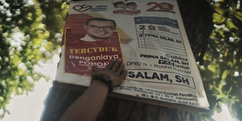 Pemasangan stiker sindiran oleh komunitas Turun Tangan Palembang kepada poster caleg yang terpasang dipohon dengan menggunakan paku.