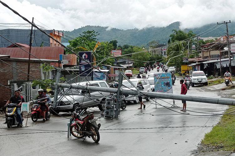 Warga melintasi tiang listrik yang melintang di jalan raya pascagempa bumi, di Mamuju, Sulawesi Barat, Jumat (15/1/2021). Petugas BPBD Sulawesi Barat masih mendata jumlah kerusakan dan korban akibat gempa bumi berkekuatan magnitudo 6,2 tersebut.