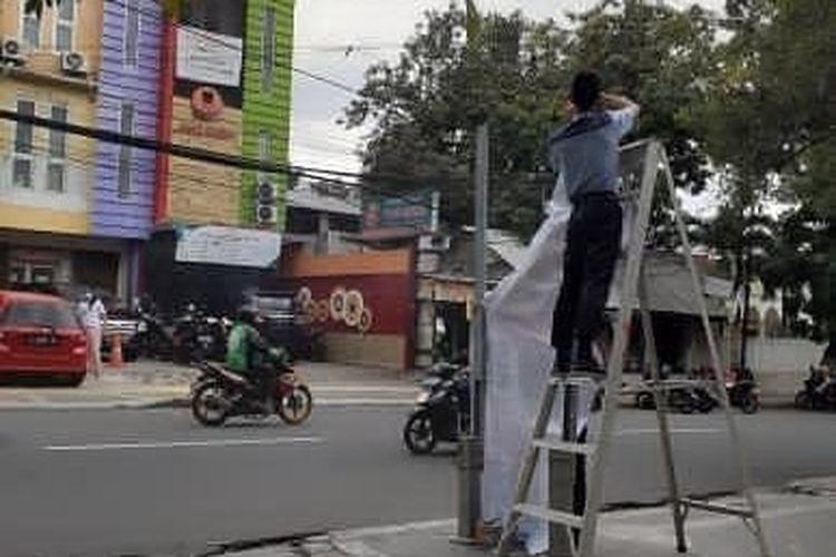 Sebuah bollard di trotoar di Jalan Tebet Raya, Tebet, Jakarta Selatan dipasangi spanduk reklame sebuah klinik kecantikan bernama DL Slim & Skin Care pada Senin (8/3/2021).