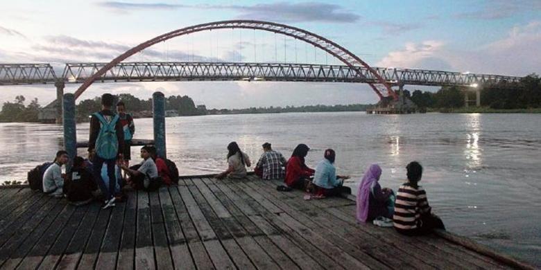 Warga Kota Palangkaraya, Kalimantan Tengah, menikmati senja di kafe tepi Sungai Kahayan, Jumat (10/4/2015). Keindahan alam, termasuk potensi wisata susur sungai, menjadi salah satu potensi wisata Palangkaraya. Namun, pengelolaan potensi itu belum optimal.