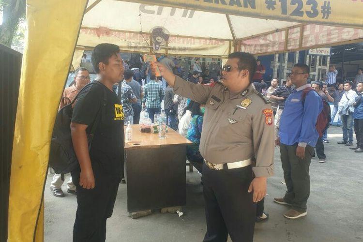 Satuan Penyelenggara Administrasi (Satpas) Aurat Izin Mengemudi (SIM) Cilenggang, Serpong, Tangerang Selatan turut melakukan upaya pencegahan virus corona. Salah satu upaya dengan melakukan pengecekan suhu tubuh terhadap pemohon SIM yang diberlakukan sejak Sabtu (14/3/2020).