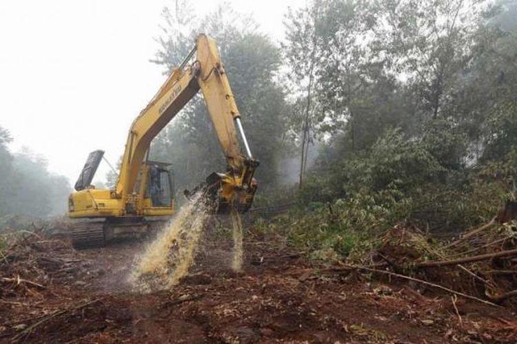 Pekerja Asian Agri menggunakan ekskavator untuk memadamkan api di area konsesi perusahaan di perkebunan kelapa sawit Rantau Baru di Pelalawan, Riau, 16 September 2015.