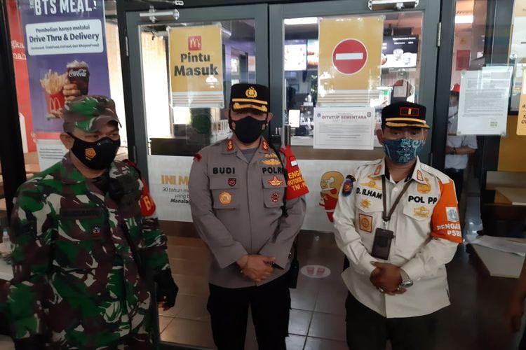 Petugas kepolisian segel McDonald's Stasiun Gambir karena mengundang kerumunan yang disebabkan oleh promo BTS Meal, Rabu (9/6/2021).