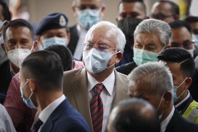 Mantan Perdana Menteri Malaysia Najib Razak (tengah), mengenakan masker berjalan bersama pendukungnya menuju ke ruang persidangan, gedung Pengadilan Tinggi Kuala Lumpur, pada 28 Juli 2020. Najib hadir dalam sidang perdana dari serangkaian dakwaan yang menjeratnya mengenai skandal 1MDB.
