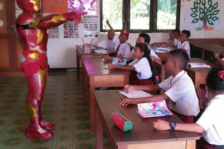 Hendra Agatama dengan kostum Iron Man mengajar di sekolah dasar Tunas Sejahtera Sungai Tawang, Kalimantan Barat