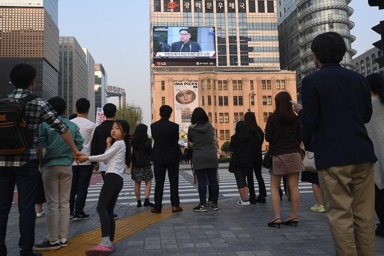 Pejalan kaki menyaksikan berita KTT Antar-Korea di televisi, Jumat (27/4/2018).