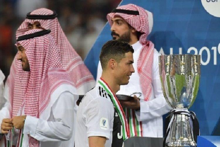 Cristiano Ronaldo berjalan di depan trofi Piala Super Italia seusai laga Juventus vs AC Milan di Stadion King Abdullah, 16 Januari 2019.