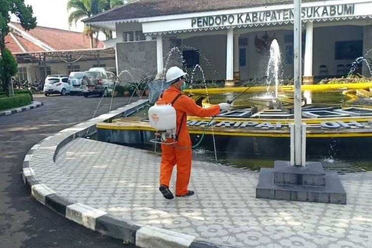 Petugas menyenmprotkan disinfektan di halaman Gedung Pendopo Sukabumi, Jawa Barat, Jumat (20/3/2020).
