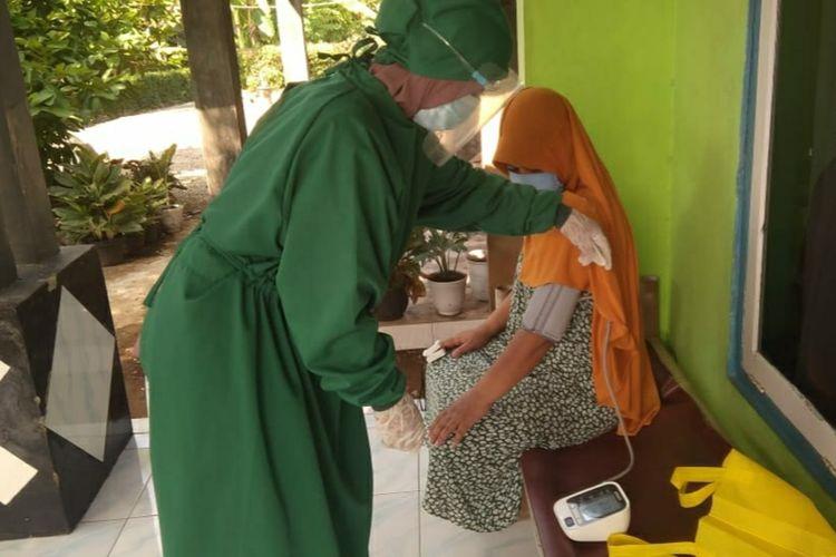 Seorang ibu rumah tangga yang menjadi nakes dadakan memeriksa kesehatan pasien Covid-19 yang menjalani isoman di Desa Karangnangka, Kecamatan Kedungbanteng, Kabupaten Banyumas, Jawa Tengah, Sabtu (17/7/2021).