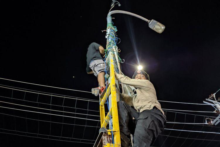 Relawan Garuk Sampah saat membersihkan tali-tali spanduk yang terikat ditiang lampu. (Foto dari Dokumentasi Garuk Sampah)