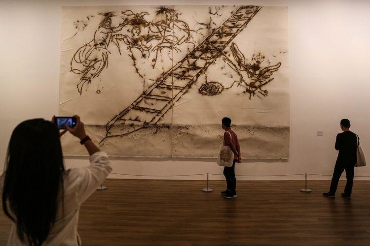 Pengunjung memotret salah satu lukisan dalam pameran bertajuk ART TURNS. WORLD TURNS. di Museum of Modern and Contemporary Art in Nusantara (MACAN), Kebon Jeruk, Jakarta Barat, Sabtu (4/11/2017). Pameran ini menampilkan 90 karya seni dari 800 koleksi Haryanto Adikoesomo mulai dari seni rupa modern Indonesia hingga seni modern dan kontemporer dari seluruh dunia. Pameran terbuka untuk umum pada 4 November 2017 hingga 18 Maret 2018. KOMPAS.com/GARRY ANDREW LOTULUNG