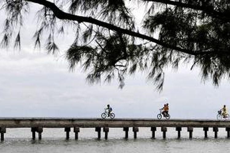 Pengunjung bersepeda menyusuri Jembatan Cinta di Pulau Tidung, Sabtu (14/3/2015). Keindahan pantai di Pulau Tidung, Kepulauan Seribu, menjadi salah satu daya tarik wisatawan untuk berkunjung ke pulau ini.