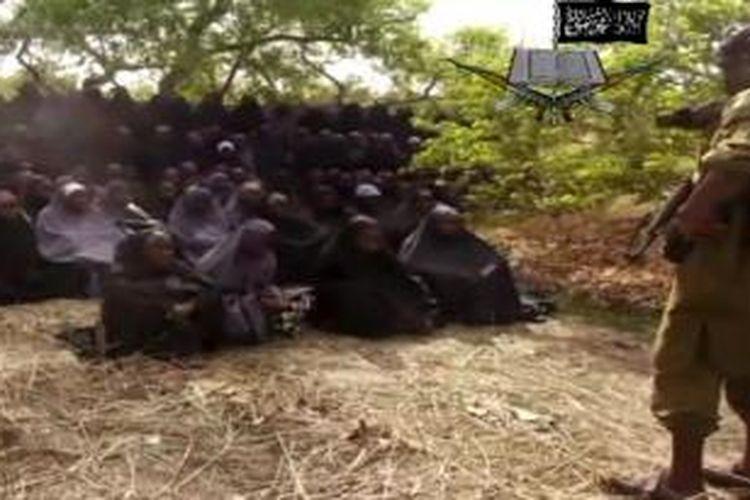 Foto ini diambil dari video terbaru yang dirilis kelompok Boko Haram. Dalam foto ini terlihat para perempuan, yang disebut Boko Haram adalah para siswi yang diculik, tengah duduk mengenakan busana Muslim. Boko Haram mengklaim para siswi itu sudah semuanya memeluk Islam dan tidak akan dibebaskan hingga pemerintah Nigeria membebaskan anggotanya yang ditahan.
