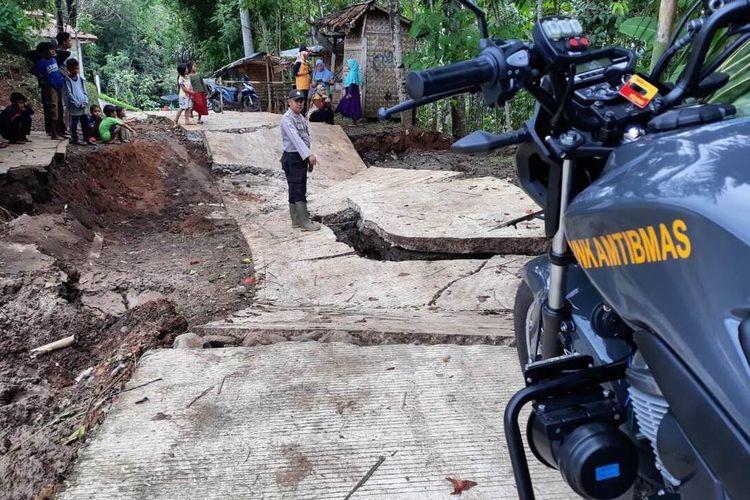 Seorang anggota Bhabinkamtibmas di wilayah Kecamatan Kadupandak memerlihatkan kondisi jalan desa yang hancur akibat pergerakan tanah, Jumat (10/01/2010)