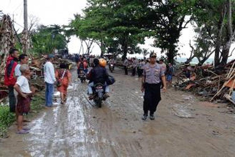 Polisi berjaga di sepanjang kawasan pantai sekitar Jalan Raya Anyer-Carita, Cinangka, Serang, Banten, Minggu (23/12/2018). Tsunami menyapu bangunan dan pondok yang ada di pantai hingga ke badan jalan.