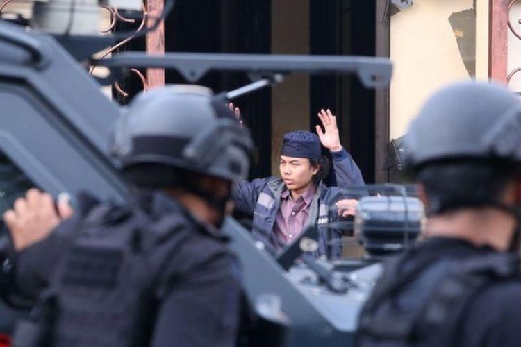 Salah seorang napi teroris mengangkat tangan saat keluar dari rumah tahanan cabang Salemba di kompleks Mako Brimob, Senin (10/05).