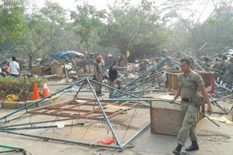 Aparat Sapol PP Pemprov DKI Jakarta membongkar kios pedagang kaki lima di lapangan Ikatan Restoran dan Taman Indonesia (IRTI) kawasan Monumen Nasional, Kamis (16/10/2014)