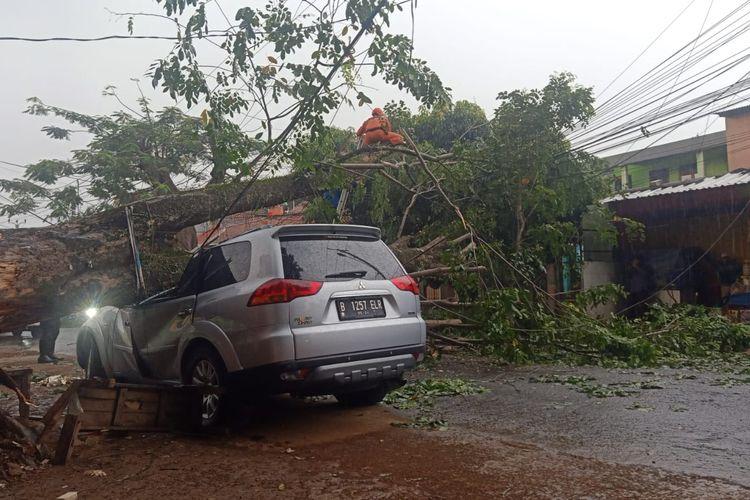 Mobil yang ditimpa pohon tumbang di Jalan Raya Kalimulya, Kelurahan Kalimulya, Cilodong, Kota Depok, pada Minggu (26/9/2021) sore.